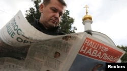 A man reads campaign literature of opposition leader Aleksei Navalny on a street in Moscow, September 3, 2013