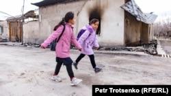 Дети проходят мимо сгоревшего дома в селе Масанчи Жамбылской области. 26 февраля 2020 года.