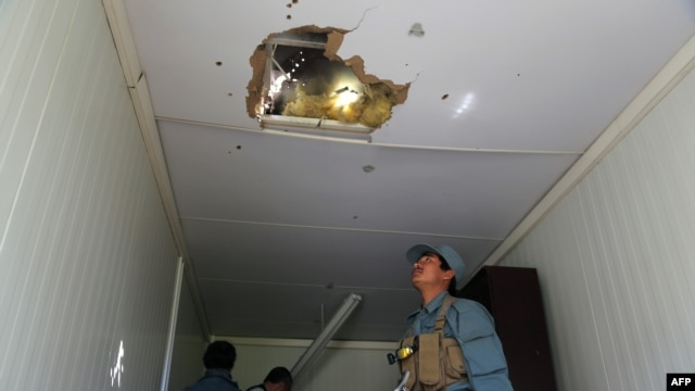 An Afghan policeman looks at a hole in the roof caused by a Taliban rocket following an attack in Ghazni Province on May 12.