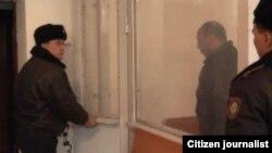 Полицейский выводит подсудимого, насмерть сбивший 16-летнюю девушку на проспекте Кунаева.