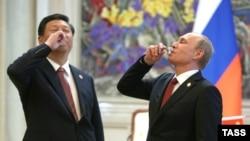 Hytaýyň prezidenti Si Jinping (Ç) rus kärdeşi Wladimir Putin bilen tebigy gaz şertnamasyna gol çekilmeginiň şanyna bada göterýär. Şanhaý, 21-nji maý, 2014.