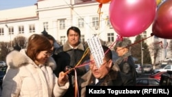 Түрмеге қамалған қазақ журналистерінің аттары жазылған шарлар ұшырғалы тұрған азаматтық белсенділер. Алматы, 11 қаңтар, 2011 жыл.
