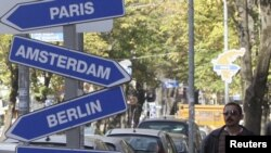 A pedestrian walks past symbolic road signs showing European cities in the Albanian capital of Tirana on November 7.