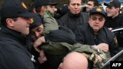 Police arrest war veterans staging a protest in Tbilisi.
