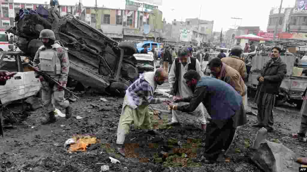 Pakistani security personnel examine the site of one of the explosions.