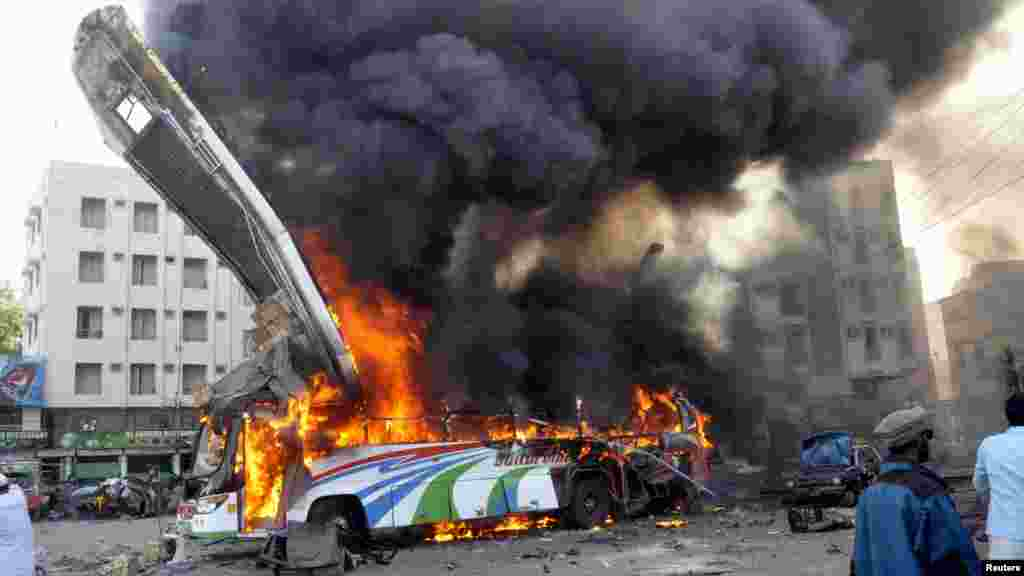 A bus is seen in flames at the site of a bomb explosion that killed six people in the Pakistani city of Karachi (Reuters)