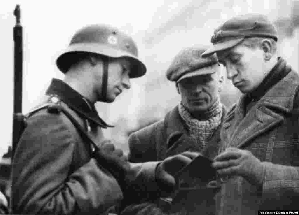 A German soldier checks the documents of two Jews.