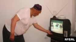 Kazakhstan - the resident of new district Sayaly is watching TV. 11Jul2009
