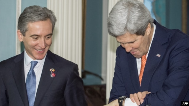 U.S. Secretary of State John Kerry (right) checks his watch as Moldovan Prime Minister Iurie Leanca looks on, before they deliver remarks to the media on March 3 at the State Department in Washington, D.C.