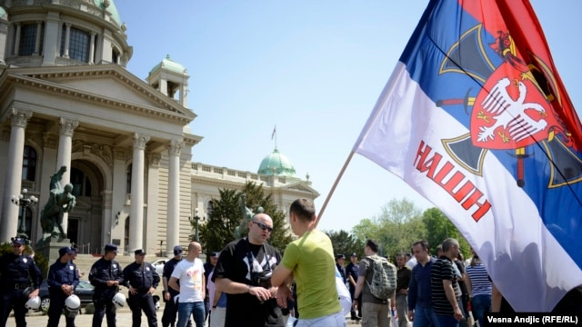"Supporters of right-wing movements shout slogans such as ""Kosovo Is Serbia"" in front of the National Assembly in Belgrade on April 26."