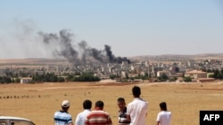 Turkey -- People look at smoke billowing in the Syrian town of Kobani from the Turkish side of the border in Suruc in Sanliurfa province, June 25, 2015
