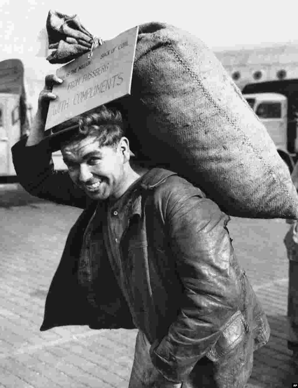 "A German worker carries away the millionth sack of coal delivered to West Berlin on September 20, 1948. The tag on the sack reads ""From Fassberg with compliments,"" crediting the British zone airfield used as a base for what became known as ""flying coal carts."""