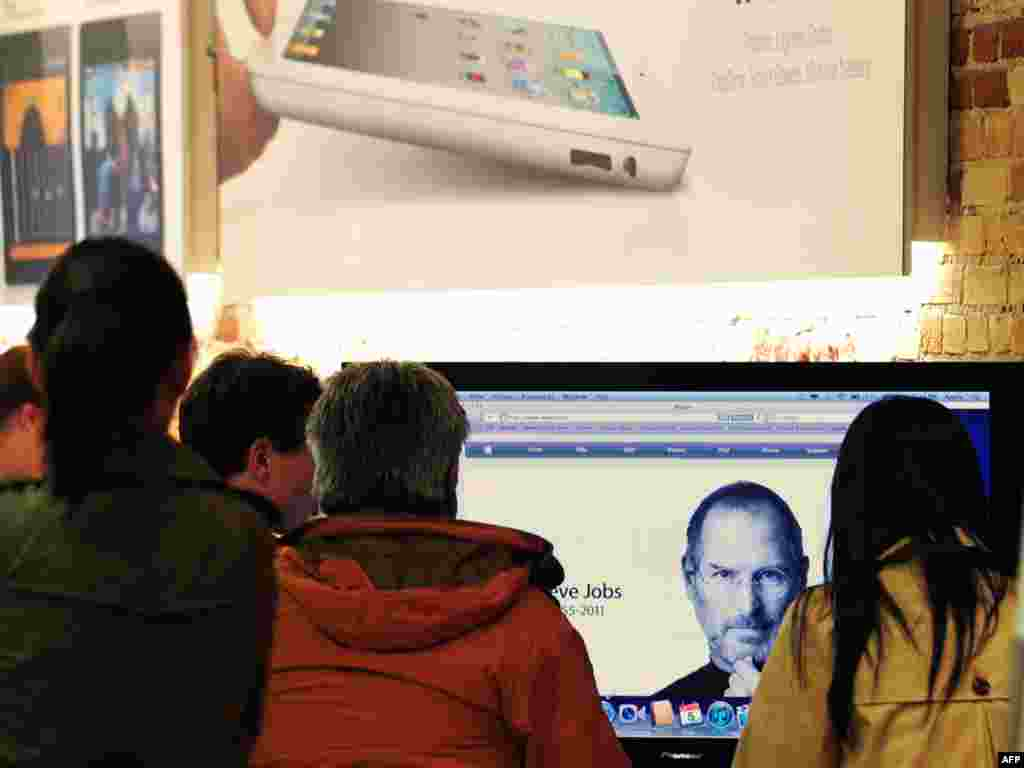 Visitors to an Apple store in Pasadena, California, view a screen from the Apple website announcing Jobs' passing on October 5.