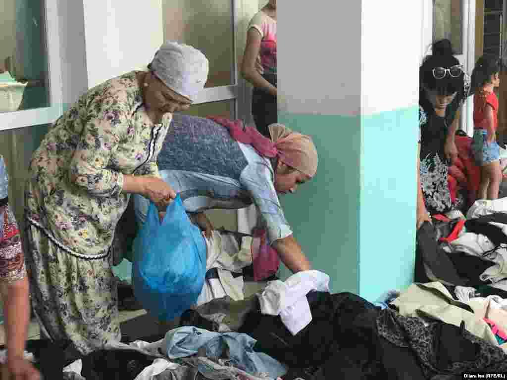 Эвакуированные жители Арыси разбирают одежду, привезенную для них волонтёрами.
