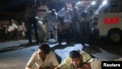 """Спасатели и журналисты укрываются от перестрелки между военнослужащими и боевиками, напавшими на базу военно-морской авиации Пакистана """"Мехран"""". Карачи, 23 мая 2011 года."""