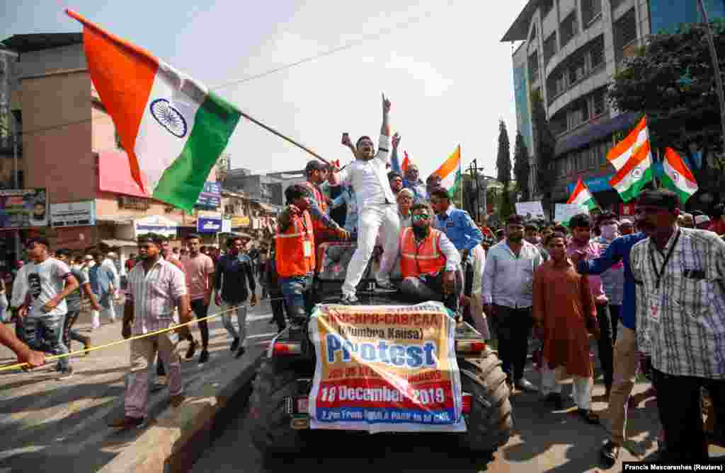 Demonstrators wave the national flag of India and shout slogans during a protest against a new citizenship law, on the outskirts of Mumbai, December 18, 2019.