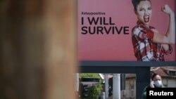 Жена с маска минава покрай билборд в София, представящ кампания за окуражаване на жителите с текстове от известни песни