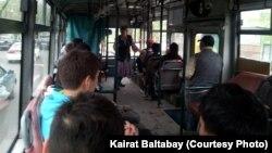 Автобуста келе жатқан жолаушылардан қайыр сұрап жүрген әйел. Алматы, 17 сәуір 2013 жыл.