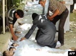 Химиялық шабуылдан қаза тапқан балалардың мәйіттері қасында жылап отырған әйелді ер адамдар жұбатып жатыр. Сирия, 21 тамыз 2013 жыл.