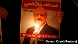 FILE: A demonstrator holds a poster with a picture of Saudi journalist Jamal Khashoggi outside the Saudi Arabia consulate in Istanbul in October.