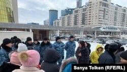 Группа заёмщиков проблемных ипотечных кредитов у башен Дома министерств, проход к резиденции президента Казахстана им перегородили бойцы спецподразделения полиции. Нур-Султан, 4 февраля 2020 года.