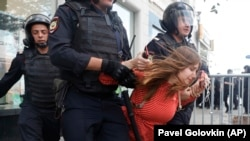 Police detain a woman during an unsanctioned rally in the center of Moscow on July 27.
