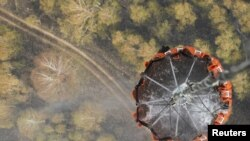 A helicopter carries water before releasing it over a forest fire in central Russia on August 10.