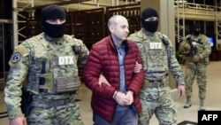 Russian-Israeli blogger Aleksandr Lapshin is escorted upon his landing in Baku after being extradited from Belarus on February 7.