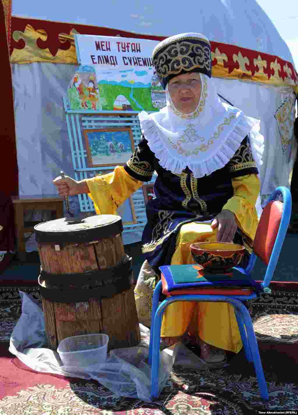 Женщина в казахском костюме показывает, как изготавливают кумыс.