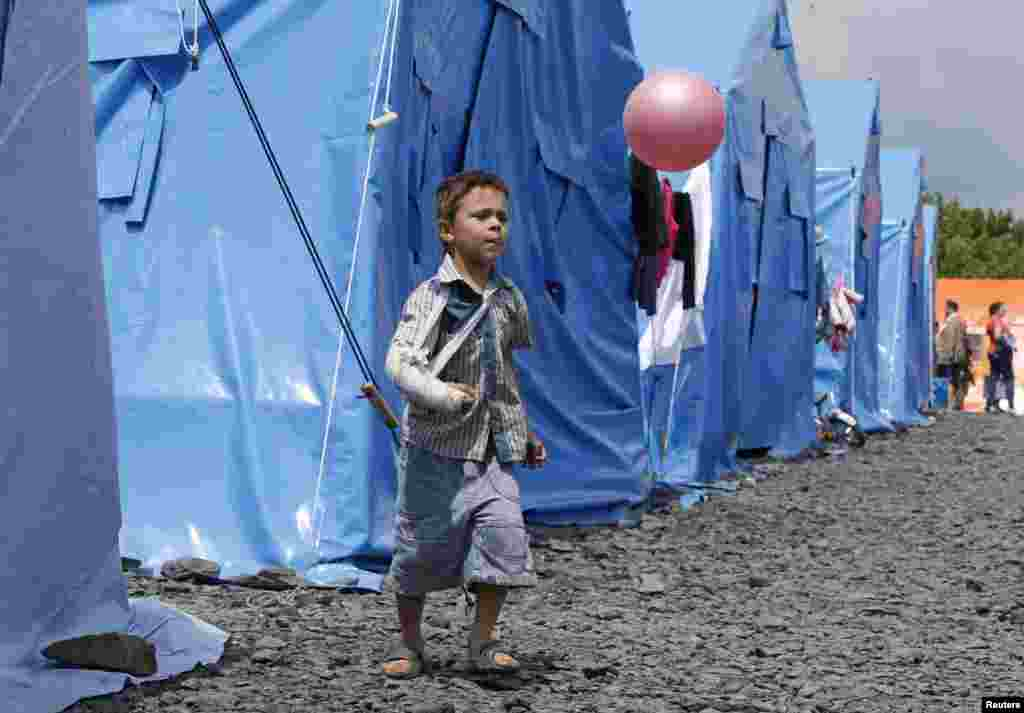 A boy plays with a ball at a temporary tent camp set up for Ukrainian refugees in the town of Novoshakhtinsk in Russia's Rostov region near the Russian-Ukrainian border on July 9. (Reuters/Sergei Karpukhin)