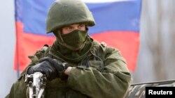Вооруженный мужчина в военной форме без опознавательных знаков, предположительно российский солдат, близ военной базы в Симферополе. 14 марта 2014 года.