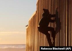 Мигрант из Гондураса взбирается на пограничную стену со стороны мексиканского города Тихуана