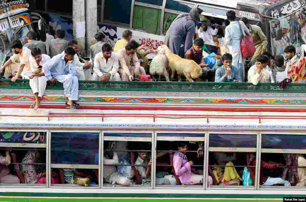 Pakistanis crowd on to a bus in Lahore as they travel to their home towns to celebrate Eid al-Fitr.