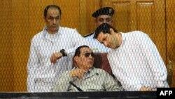 Misirin keçmiş prezidenti Hosni Mubarak və oğulları Alaa (Sağda) və Gamal məhkəmədə