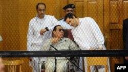 Keçmiş prezident Hosni Mubarak və oğulları Alaa (sağda) və Gamal 2013-cü ildə məhkəmə zamanı