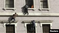 محتجون مصريون يحاولون الدخول الى مبنى قرب وزارة الداخلية لإخماد حريق شب في أحد طوابقه