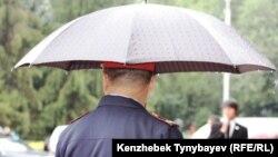 Қолшатыр ұстаған полиция қызметкері. Алматы, 12 қыркүйек 2010 жыл. (Көрнекі сурет)