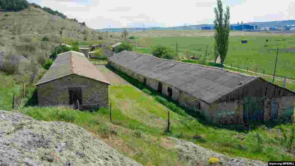 Старая колхозная ферма без признаков жизни. По одной информации, ее построили в начале XX столетия немецкие колонисты из Швейцарии, развивающие в долине Малого Салгира молочное животноводство. Вдали виднеется здание Таврической ТЭС