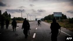 Пророссийские сепаратисты идут по дороге недалеко от Донецка. 18 августа 2014 года.
