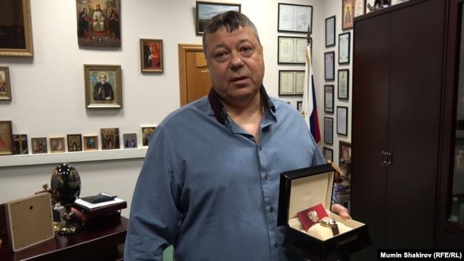 Сергей Михайлов демонстрирует часы, подаренные президентом РФ