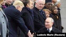 АҚШ президенті Дональд Трамп пен Ресей президенті Владимир Путин қол алысып тұр. Париж, 11 қараша 2018 жыл.