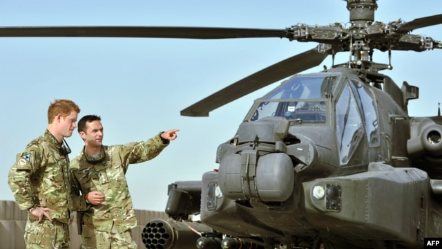 Britain's Prince Harry (left) is shown an Apache helicopter upon his arrival at Camp Bastion, in Afghanistan, on September 7.