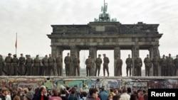 ГДРдин чек арачылары Бранденбург дарбазасынын алдындагы Берлин дубалынын үстүндө тизилип турушат. 11-ноябрь 1989
