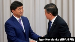 New Prime Minister Mukhammetkalyi Abylgaziev (left) is congratulated by President Sooronbai Jeenbekov in parliament in Bishkek on April 25.