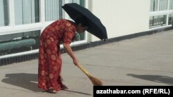 turkmenistan. woman with brooms are cleaning streets ahead of Elder's Council in Turkmenabat
