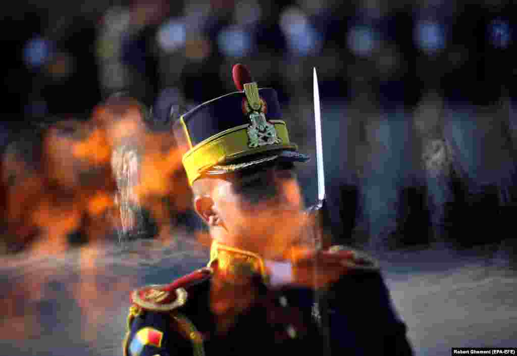 A Romanian honor guard soldier stands at attention as seen through the eternal flame at the Unknown Soldier Memorial during the Romanian Army Day celebration in Bucharest. (EPA-EFE/Robert Ghement)