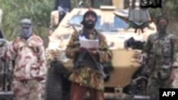 «Боко Харам» басшысы Әбубакар Шекау (ортада) үндеу жасап тұр. Видеодан скриншот.
