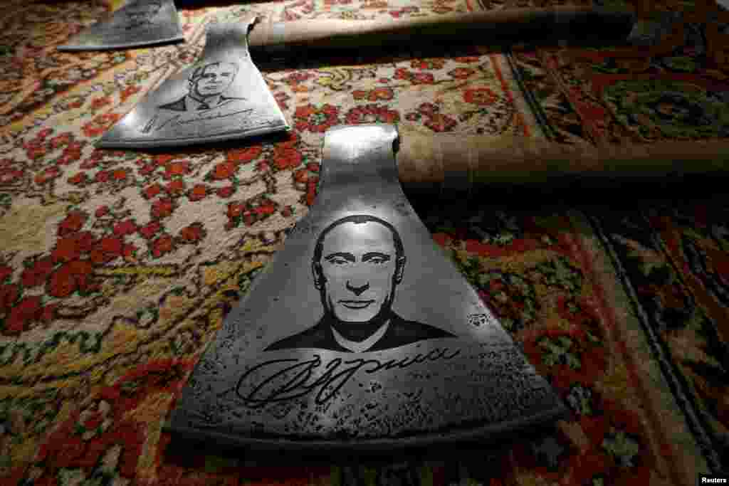 An ax featuring a portrait of Russian President Vladimir Putin by Russian artist Vasily Slonov is seen during an exhibition titled Quilted Cavaliers Of The Apocalypse in Moscow. (Reuters/Sergei Karpukhin)