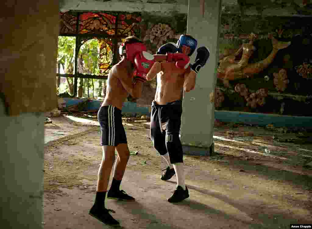 Boxing trainer Lizbar Jalogua spars with a young student in a ruined Soviet-era resort in Gagra.