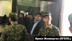 Куандык Бишимбаев (за спинами охранников справа) во время судебного разбирательства по его делу, 7 ноября 2017 года.